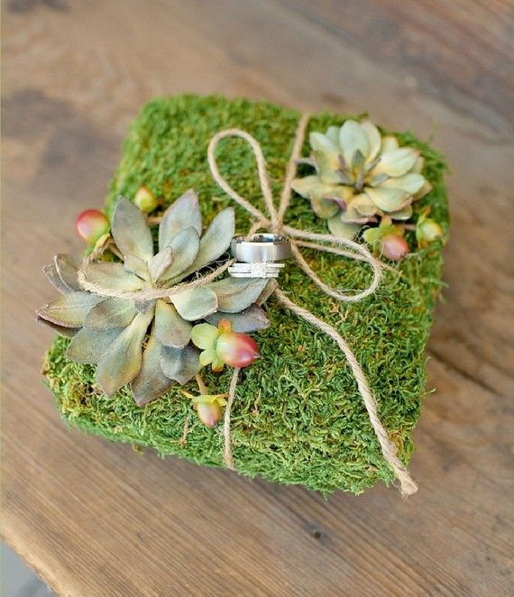 """Moss Covered Ring Pillow - Natural preserved sheet moss is wrapped around styrofoam to create this ring bearer """"pillow."""" It is adorned with realistic faux """"hens and chicks"""" succulents and hypericum berries. Tie wedding bands with the natural jute twine."""