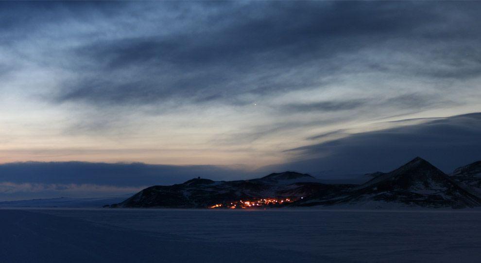 Ross Island, visto desde la isla de Negro, a unos 25 kilómetros de distancia. El resplandor de las luces de la Estación McMurdo (Estados Unidos) se puede ver, y el resplandor del sol justo debajo del horizonte crea un amanecer que durará semanas.