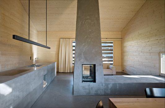 Der wohnraum wird durch zwei markante objekte geprägt den im zentrum des raumes aufragenden pyramidenförmigen kamin mit sitzbank die den raum in wohnen