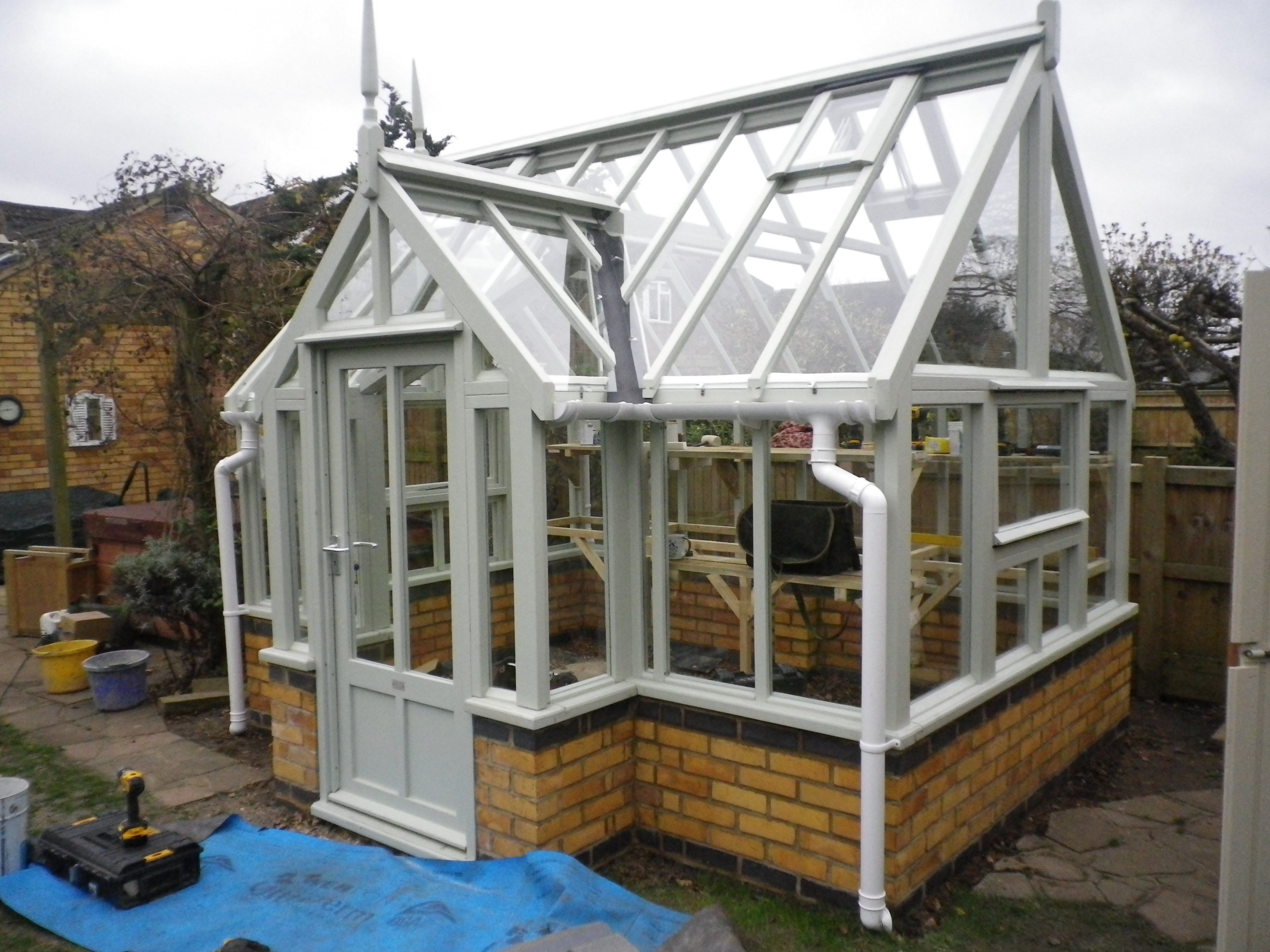 Wooden greenhouse on dwarf brick wall Wooden greenhouses