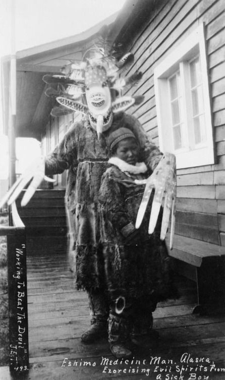 Yup'ik shaman exorcising evil spirits from a sick boy, Nushagak, Alaska, 1890s