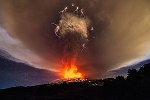 O céu da noite acende-se sobre a costa leste da Sicília como Voragine cratera do Etna entra em erupção Mount pela primeira vez em dois anos