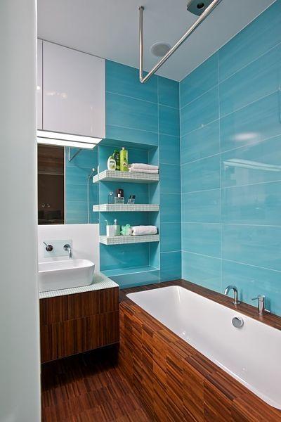 Koupelna je pýchou bytu. Podlaha je z tmavého dřeva a stejný materiál je použit na obložení vany a umyvadlové skříňce.