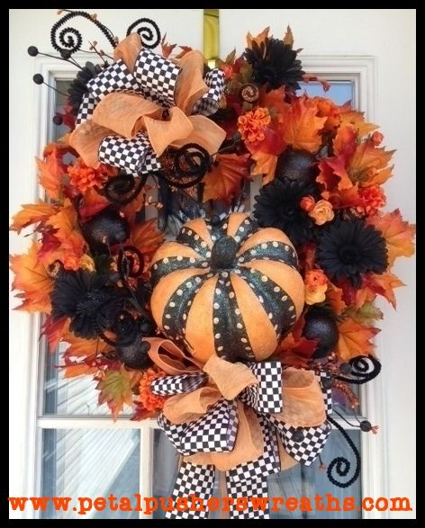 """""""A Spooky Surprise"""" Halloween Wreath Adorable Halloween wreath filled with lush fall leaves, black Gerbera daisies, glittering sprays and ornaments, designer ribbon, and a whimsical pumpkin. This stunning wreath measures approx: 26"""". Free US shipping on all Halloween wreaths!"""