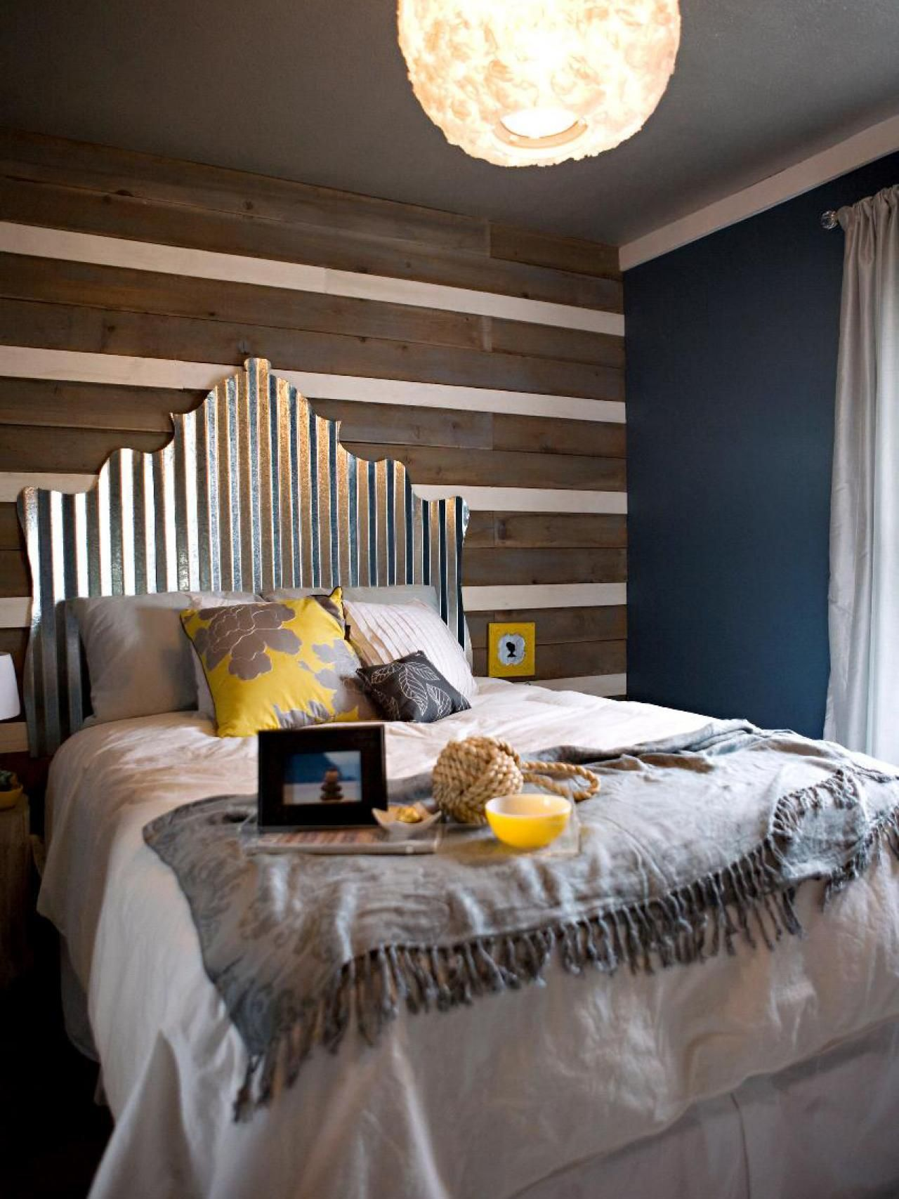 378f4a653e01 An industrial-style metal headboard is cut in a traditional shape and  positioned against a wood-beam accent wall to create a rustic chic bedroom.