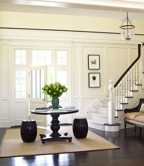 An antique mahogany table and teak stool bring visual weight to this light-filled entryway - Traditional Home® / Photo: Tria Giovan / Design: Ken Gemes