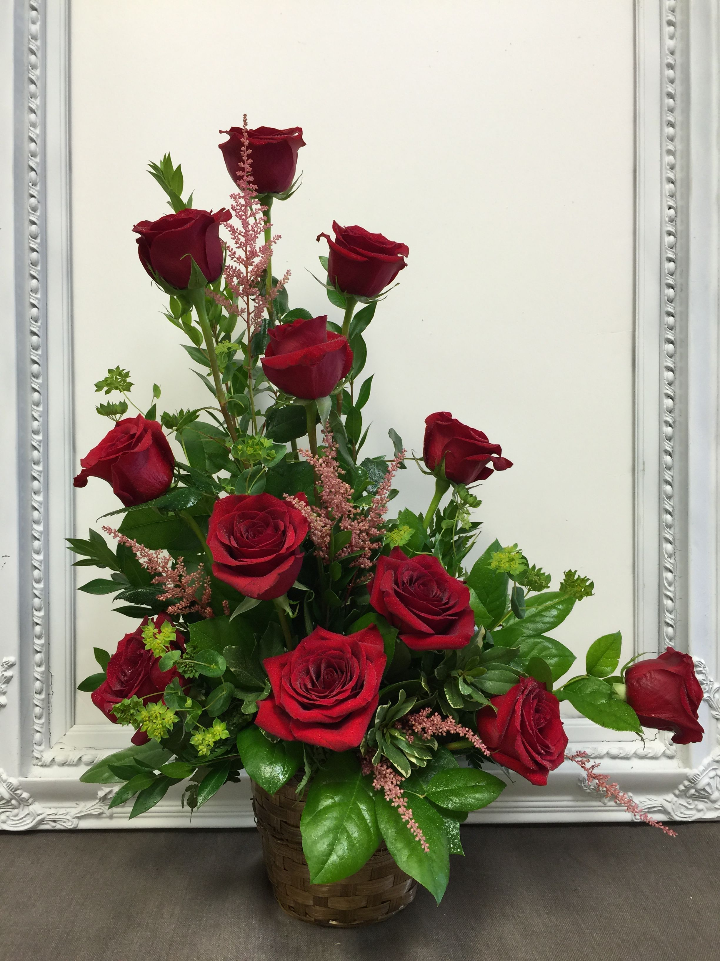 A dozen red roses beautifully arranged one sided in a