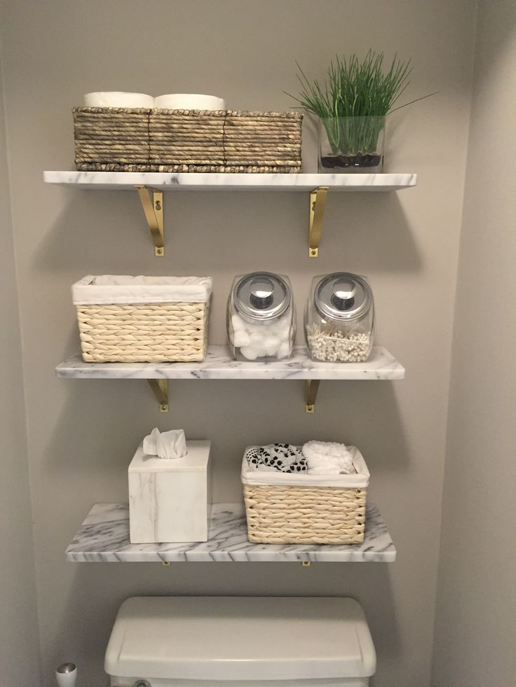 Photo of Marble wall shelves from CB2. Wooden shelves and toilet paper in a basket. Farmhouse …