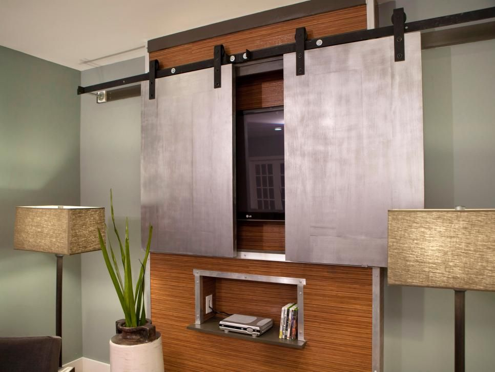 this media cabinet features sliding steel doors which hide the roomu0027s flatscreen tv