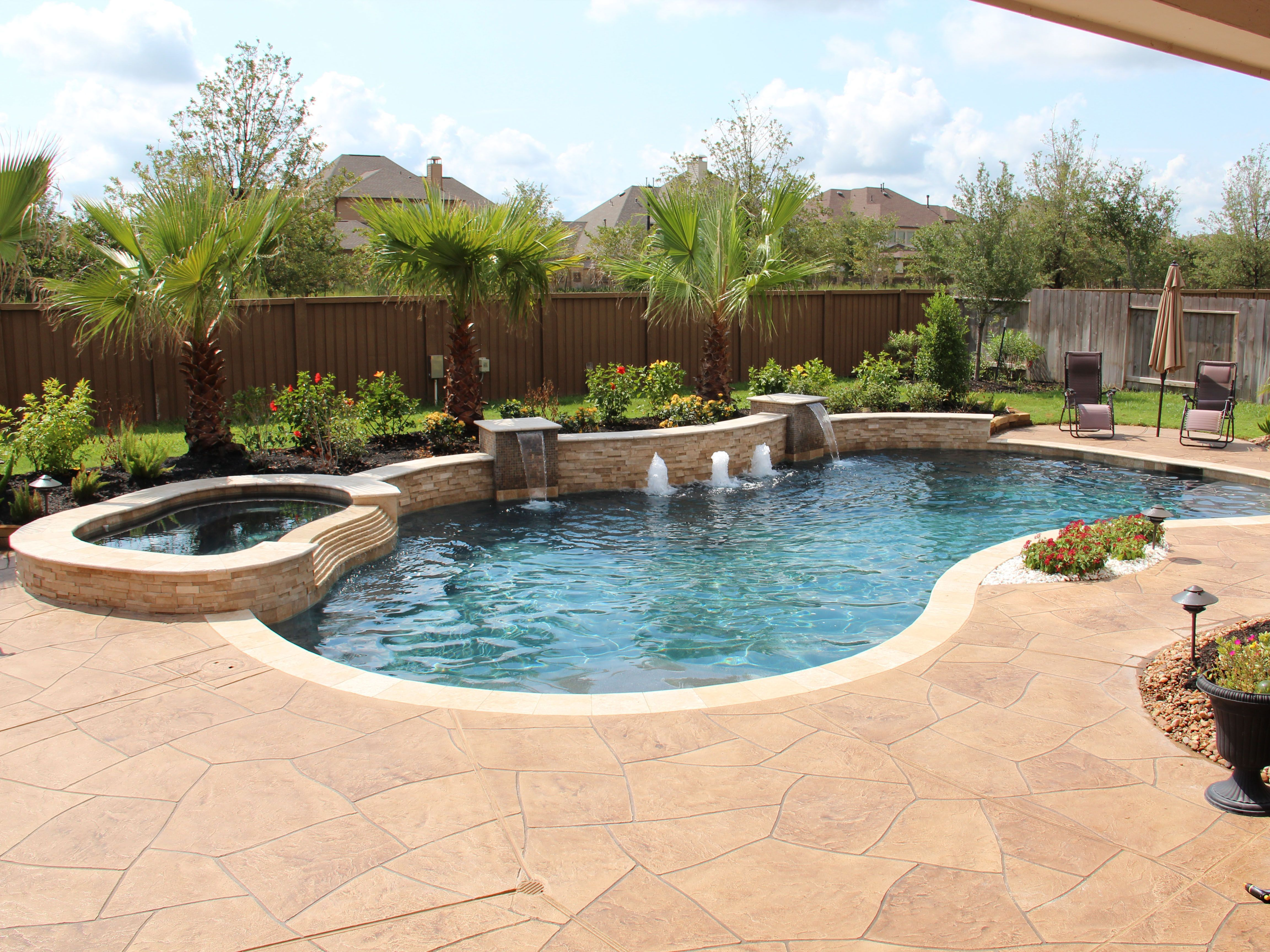 This is the same pool in image 114. Here is a full view of the pool and patio surface. From this angle you can see that the raised back beam is higher in the middle and that it is curved. The patio is a textured overlay pattern with travertine coping. #backyardremodel