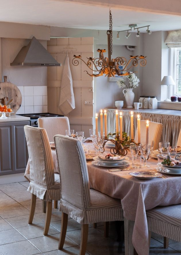 Striped upholstered dining chairs around laid table in country kitchen. The walls are painted in Elephants Breath and the cupboards in Charleston Grey both by Farrow & Ball ~ Kate Forman's Farmhouse Kitchen