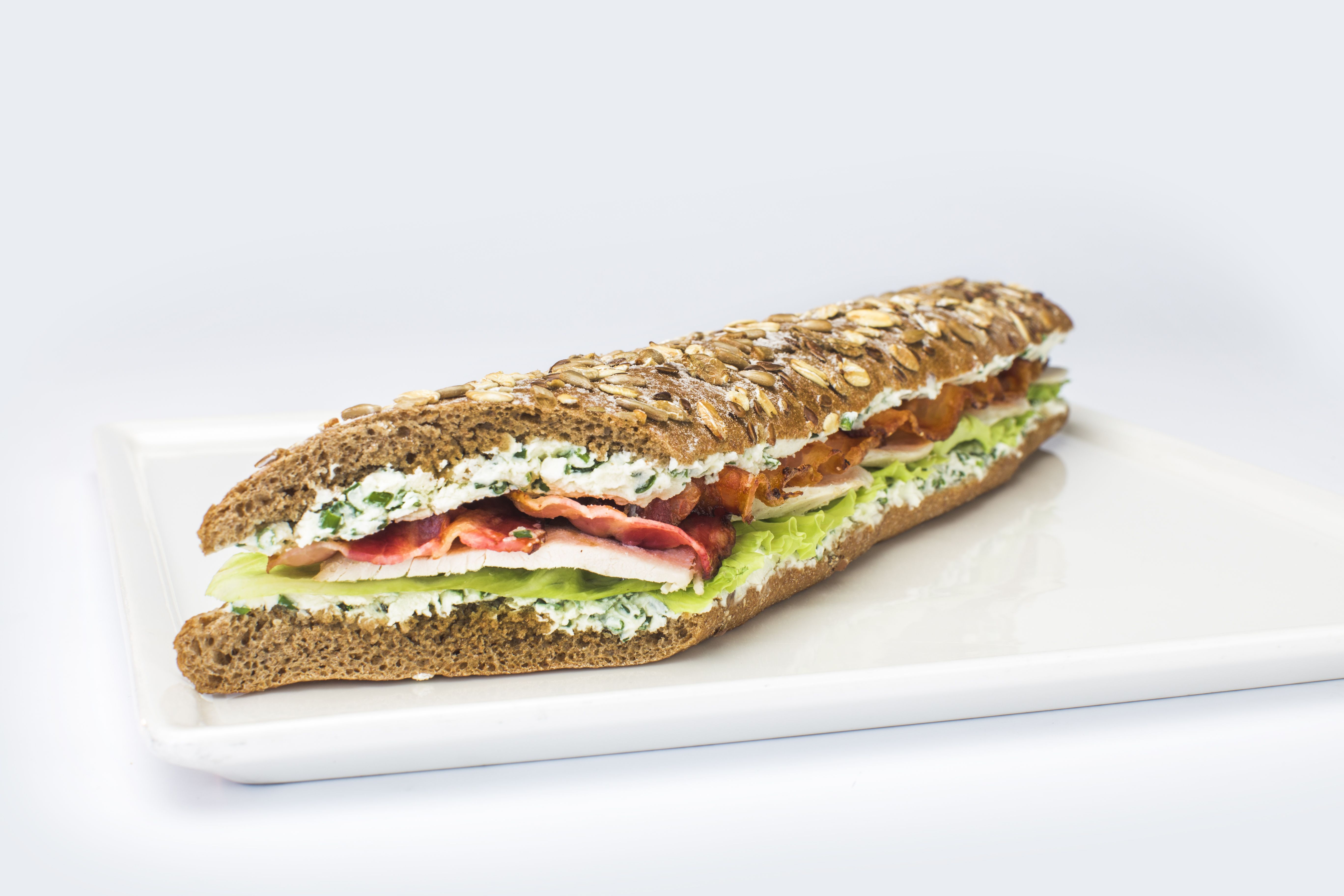 TURKEY AND CRISPY PANCETTA BAGUETTE - Whole wheat baguette, turkey breast in vacuum with bouquet garni, oven baked crispy pancetta, cream cheese with chives and iceberg salad.