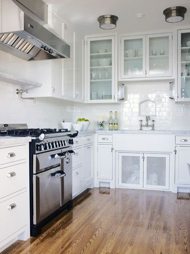 White glass front kitchen cabinets marble countertops subway tiles backsplash pot filler farmhouse sink nickel bridge faucet and flushmount lights also