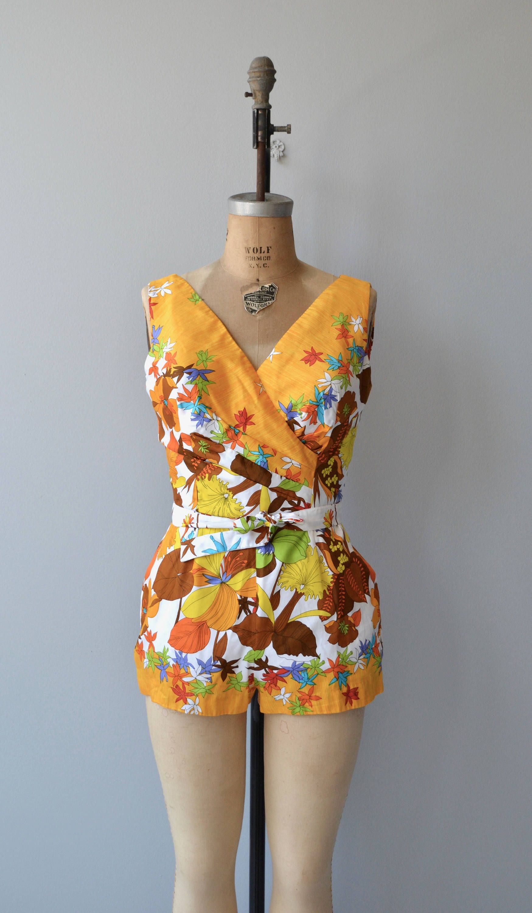Vintage 1960s super fun cotton swimsuit/playsuit with fantastic floral print, wideset shoulders, surplice gathered bodice, matching belt, boy shorts and metal back zipper. ✂-----Measurements fits like: small/medium bust: 38-40 waist: 26-27 hip: 38 length: 31 brand/maker: Jacobsons condition: excellent ✩ layaway is available for this item to ensure a good fit, please read the sizing guide: http://www.etsy.com/shop/DearGolden/policy ✩ more lingerie | ...