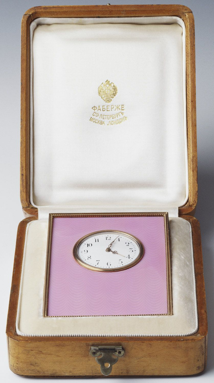 Fabergè - Desk clock, Creator: Henrik Emanuel Wigström ) (workmaster). ca, 1903 - 1913. Rectangular strut desk clock of gold with pink guilloché enamel, the gold mounted bezel contains a white enamel face with black arabic numerals, pierced gold hands; the whole has an ivory back. This clock retains its original holly wood box, lined with silk and velvet. Mark of Henrik Wigström; gold mark of 56 zolotniks and silver mark of 88 and 91 zolotniks (1908-17); Fabergé in Cyrillic characters.