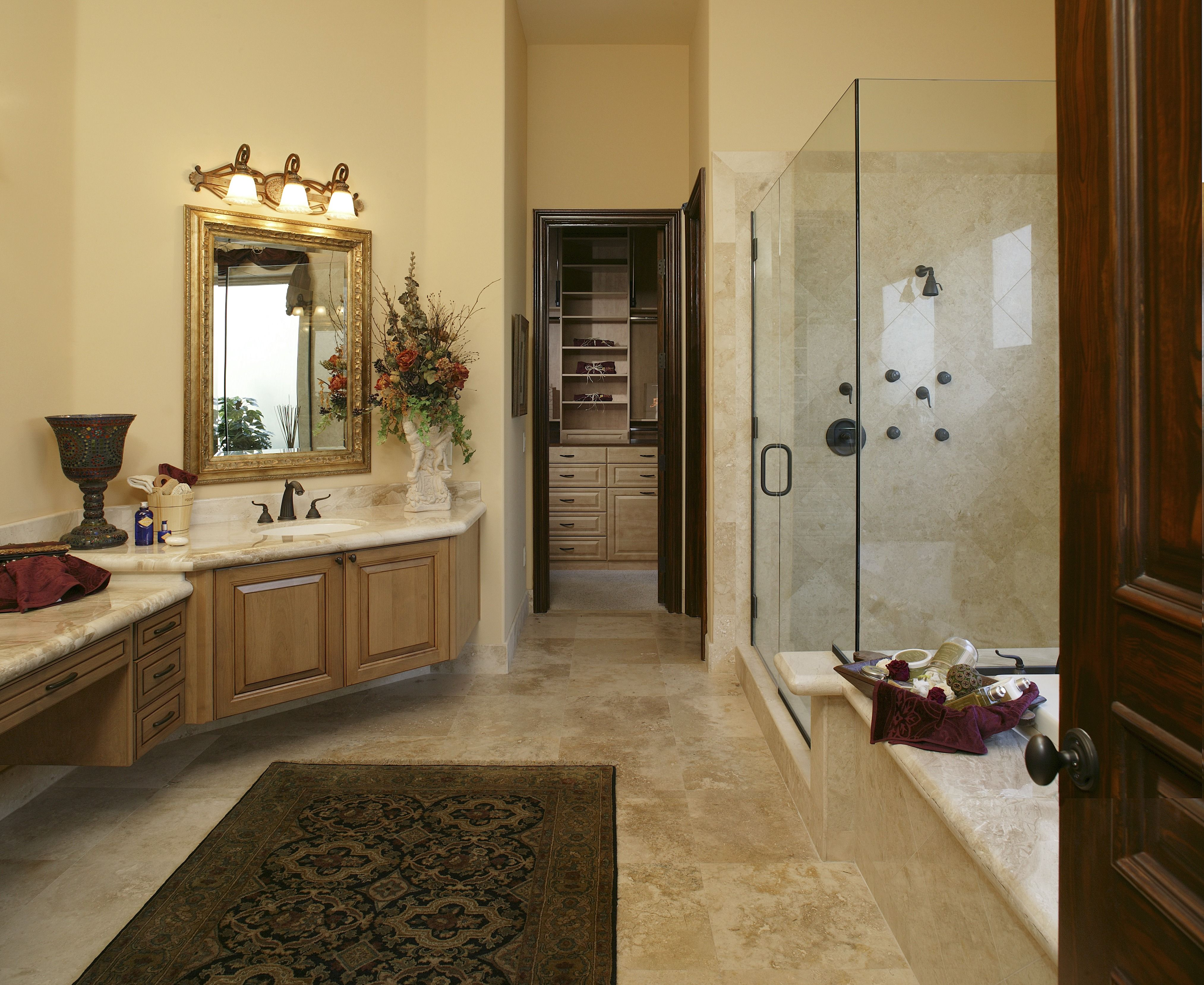 The neutral walls, tile floor and glass shower door make this ...