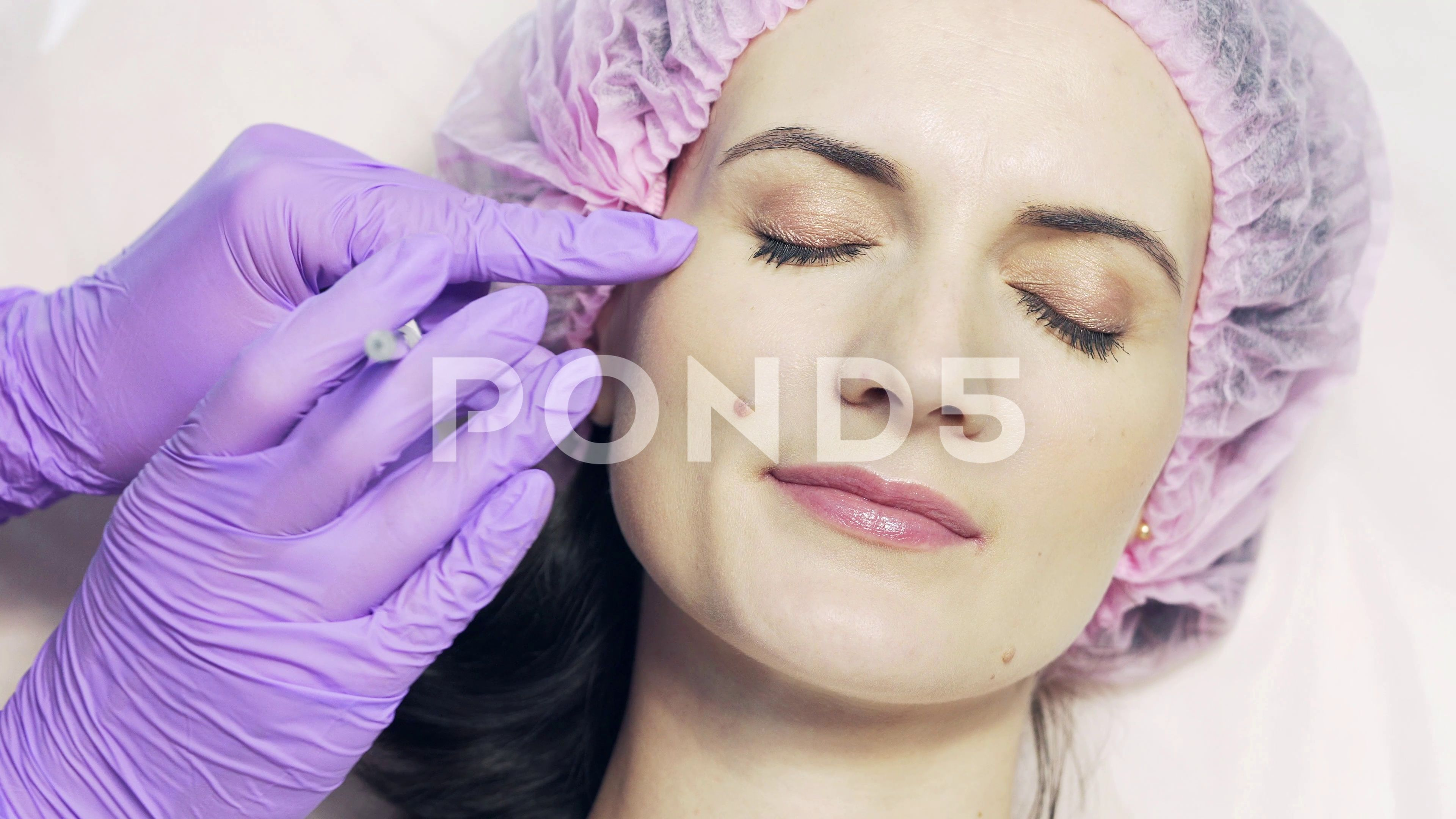 Patient in medical cap receives facial injection in beauty salon Stock Footage receivesfacialcapPatient