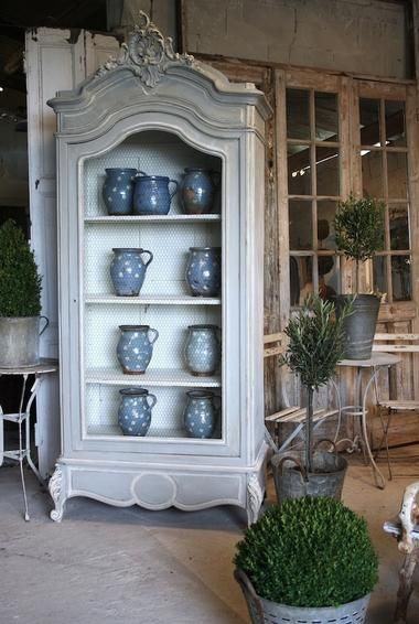 open armoire with lovely blue pottery. . .