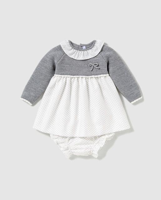 fee6c9500 Vestido combinado de tricot en color gris y falda estampada a contraste.  Tiene manga larga y cuello babero. Detalle de lazo en el delantero.