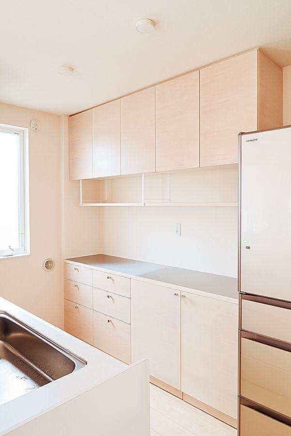 メープルの風合いが美しいキッチンエリアの収納家具を制作させて頂きました。 白を基調としたお部屋に合わせて家具類も白に統一されていましたが木の表情を取り入れる事で より空間の印象が奥深い物になると思い染色したメープルの突板での制作をおすすめさせていただき ました。 キッチンの背面収納は2メートルを超える本体幅を設定し十分な収納量と作業スペースを確保し、さらにキッチン手前のカウンター下にも膝上程度の収納を制作しました。