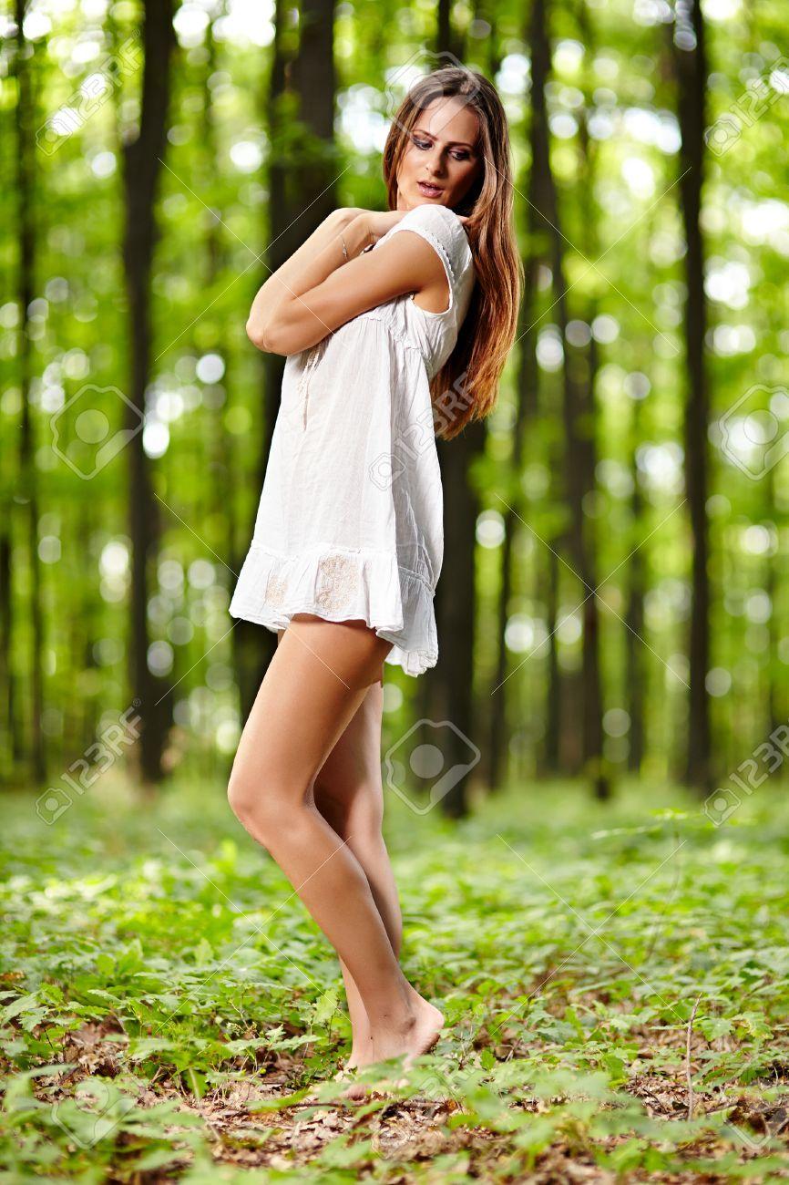 ee24aabca Mujer joven hermosa con un vestido blanco en un bosque en un día de ...