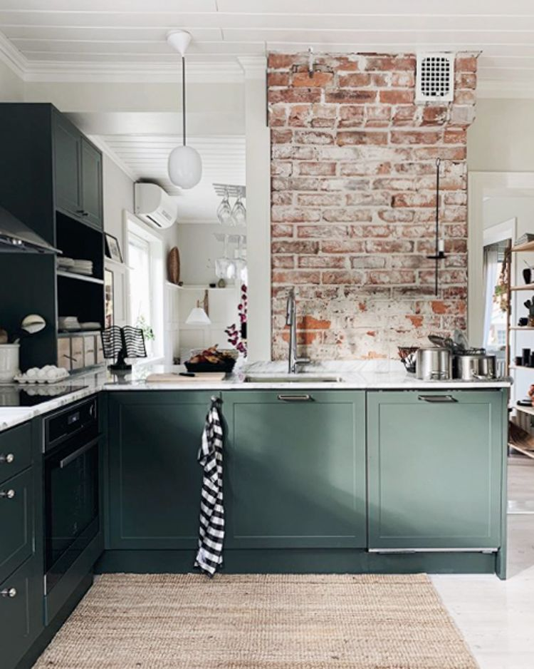 Photo of Green kitchen with exposed brick walls