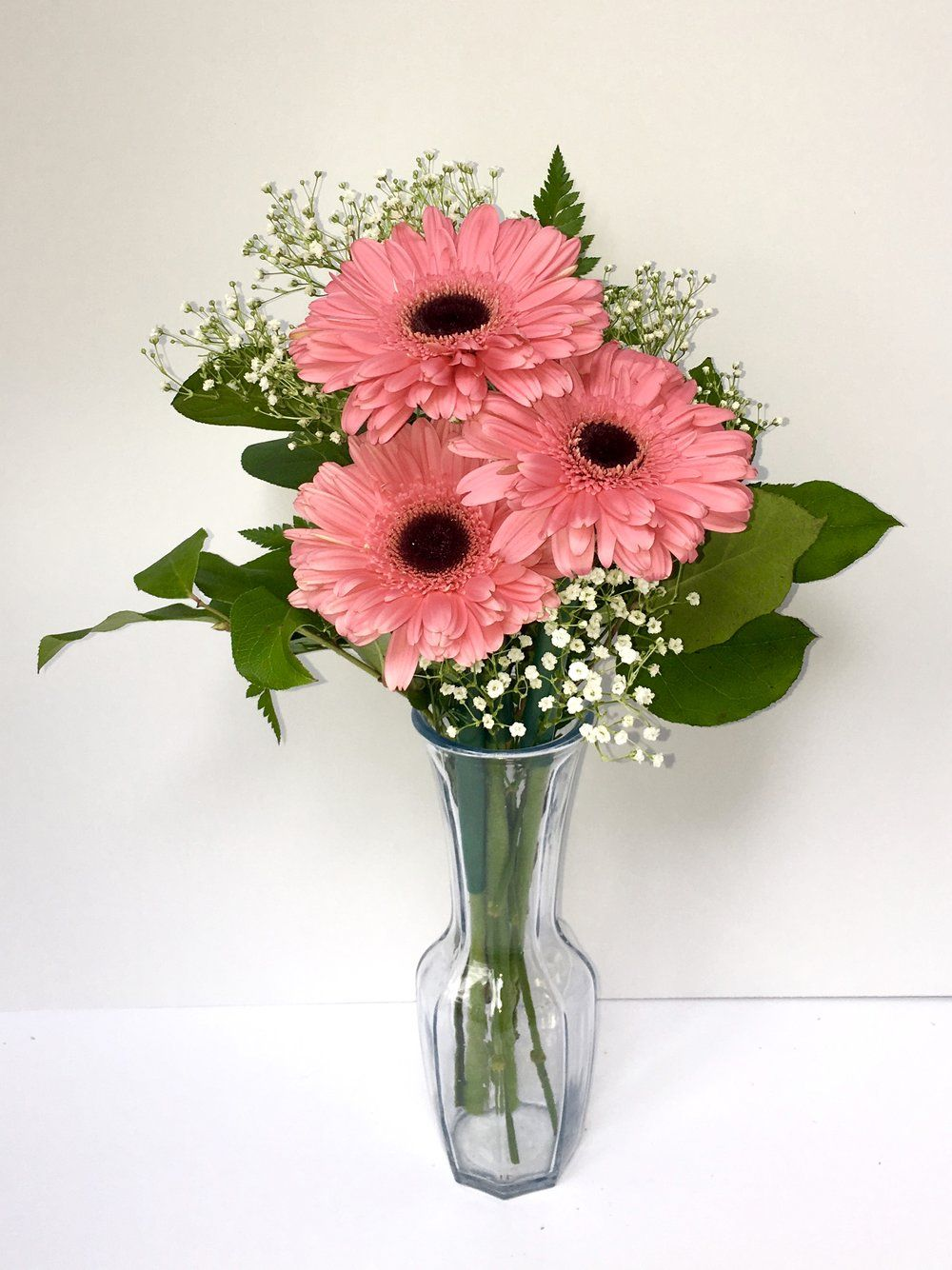Beautiful Vase Featuring Three Pink Gerber Daisies With Baby S Breath And Green Flower Arrangements Simple Wedding Centerpieces Daisy Centerpieces
