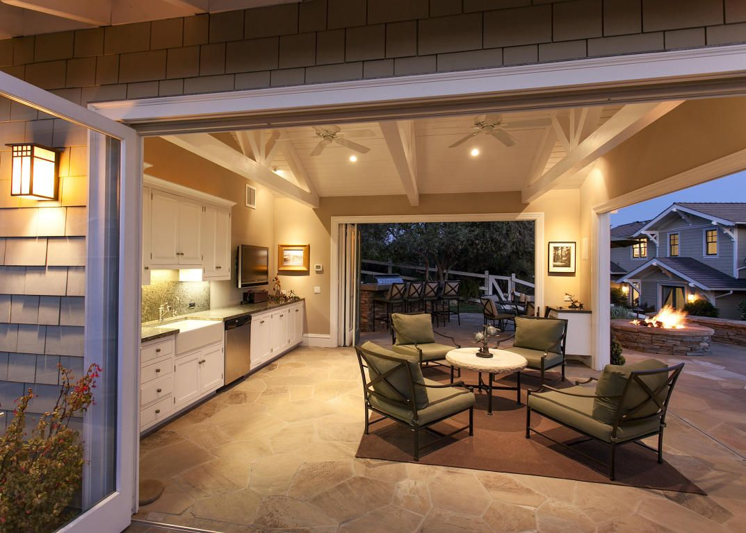 Dramatic pool cabana with half bath, outdoor shower, fire pit, and outdoor kitchen.