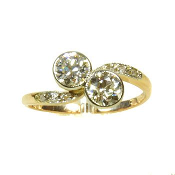Item #0746 Finely Pretty Diamond Crossover Ring  Two twinkling hand-cut diamonds snuggle closely together in a simple rubover setting of platinum on an 18ct yellow gold band. Sparkly diamond-set shoulders enclose the design.Approximate diamond weight 80pts. Circa 1920's.  £2750.00
