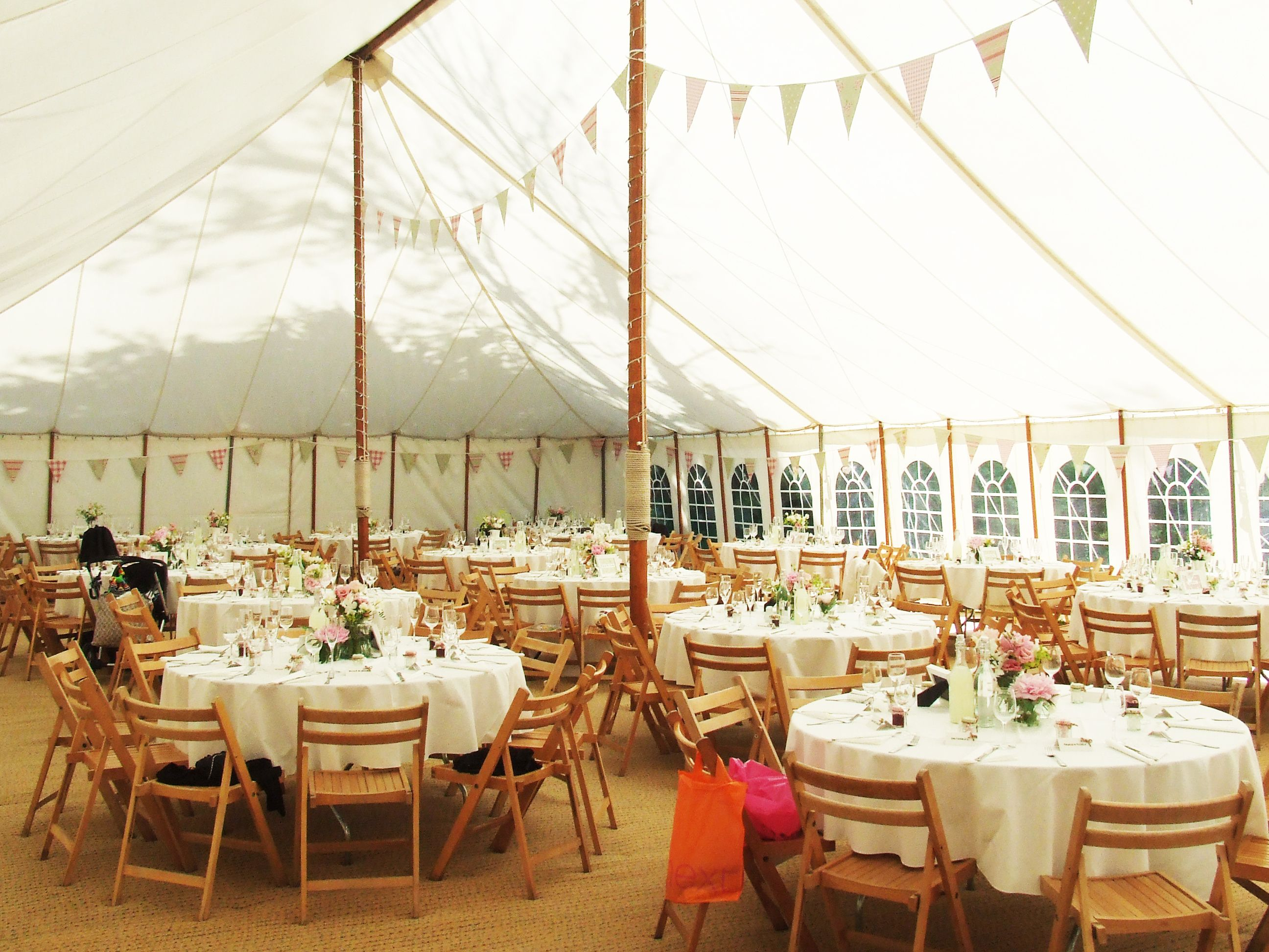 Unlined Marquee With Bunting Wooden Folding Chairs And Peonies Wedding ReceptionWedding