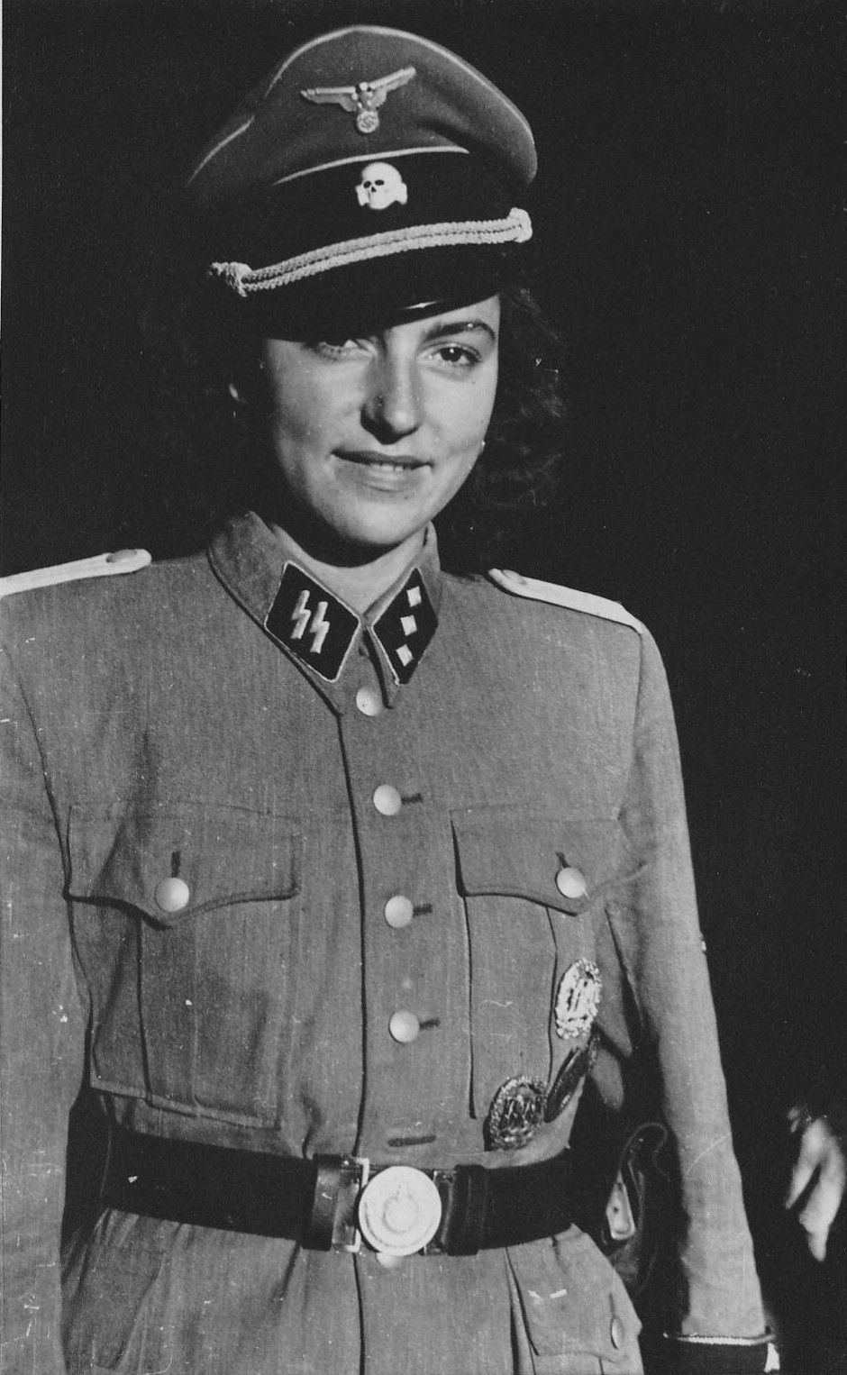 "A young lady dons the uniform of a captin in the Waffen SS. Since no women served with the Waffen SS, this is most likely a ""modeling"" photo for undetermined purposes."