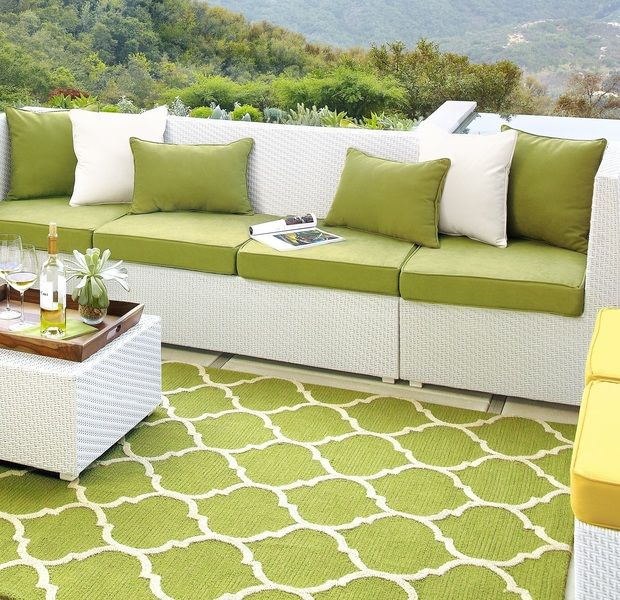 deck the patio in style with a colorful green area rug and white outdoor furniture - Patio Rugs