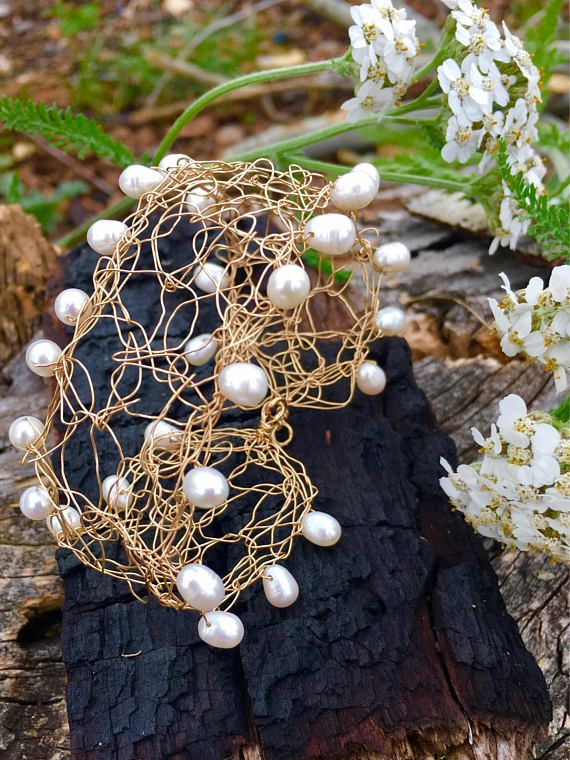 This bracelet is crocheted by hand out of 14k yellow gold fill wire with white tear drop pearls strung in along on the edges. It appears delicate and ornate like a lace cuff. This bracelet is very comfortable and light weight. It is a conversation piece and It can be worn with most anything. Bracelet measures 7 1/4 inches from clasp to loop in its natural state. Has some ability to form for a loose or tighter fit by using slight pulling and pushing for the fit you desire. All Desarium Je...