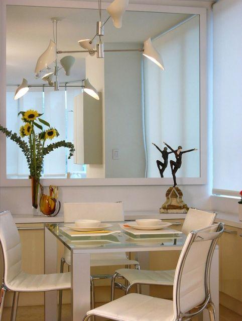 un comedor moderno y con poco espacio al que se le ha colocado un espejo