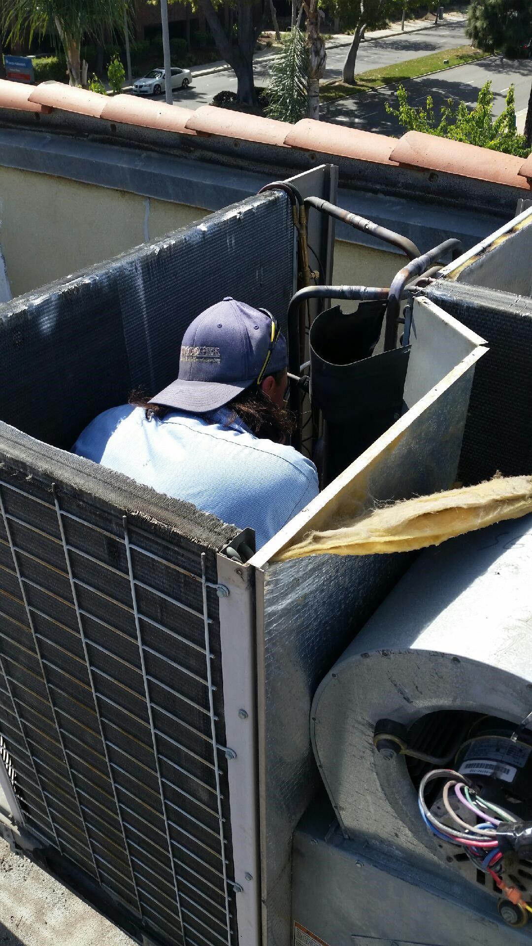 Corey inside a package unit, welding a leak in the copper