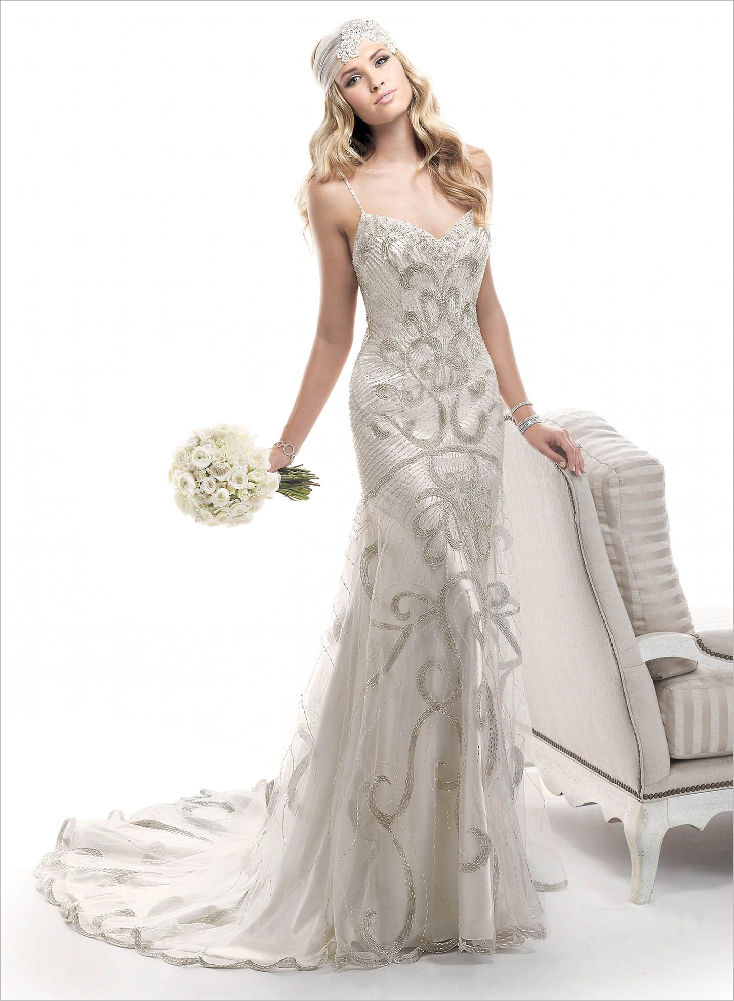 Chancey - by Maggie SotteroMetallic embroidery coupled with intricate beaded patterns create this stunning fit and flare gown, over rich Evita Satin. Complete with sweetheart neckline and finished with zipper back closure. COLORS AVAILABLE Alabaster with Silver Accent (shown), Champagne with Silver/Gold Accent