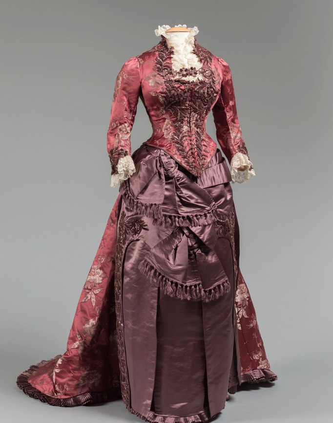 Dinner dress from around 1875 was made by the House of Mme. Levillion, Paris, and likely worn by Sara Jane Wilcox (Mrs. Peter Marshall) Hitchcock. It is made of burgundy silk brocade and purple silk satin with beadwork.