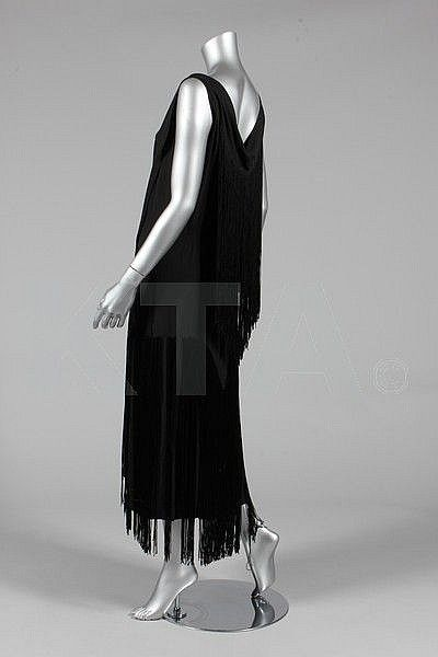 A black crepe de chine cocktail dress with fringes, circa 1926, full-length, with two scarf-like fringed panels to front and fringed capelet panel to the back, deep fringes to hem, bust 97cm, 38in; together with a pale blue-grey silk kimono-jacket with fringes to hem and angular cuffs (2) Chanel produced a knee-length fringed cocktail dress with similar capelet detail in 1926.