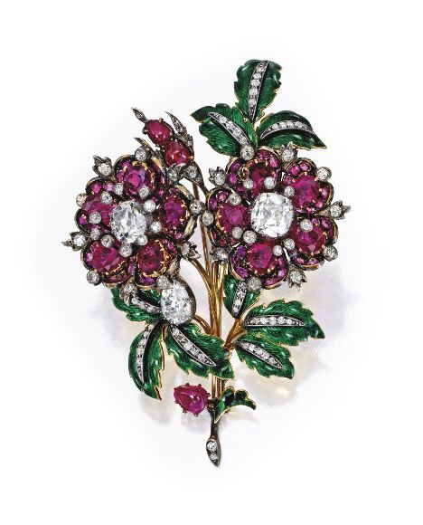 From the Collection of Mrs. Charles Wrightsman - Silver-Topped-Gold, Ruby, Diamond & Enamel Brooch, Circa 1870 - Designed as intertwining flowers, the two flowerheads centered by old mine-cut diamonds weighing approximately 5.75 carats, one flowerhead suspending a pear-shaped diamond drop weighing approx. 2.25 carats, the flower petals set with numerous cushion-cut & oval-shaped rubies, accented throughout by numerous old mine, old European & rose-cut diamonds weighing approximately 2.60…