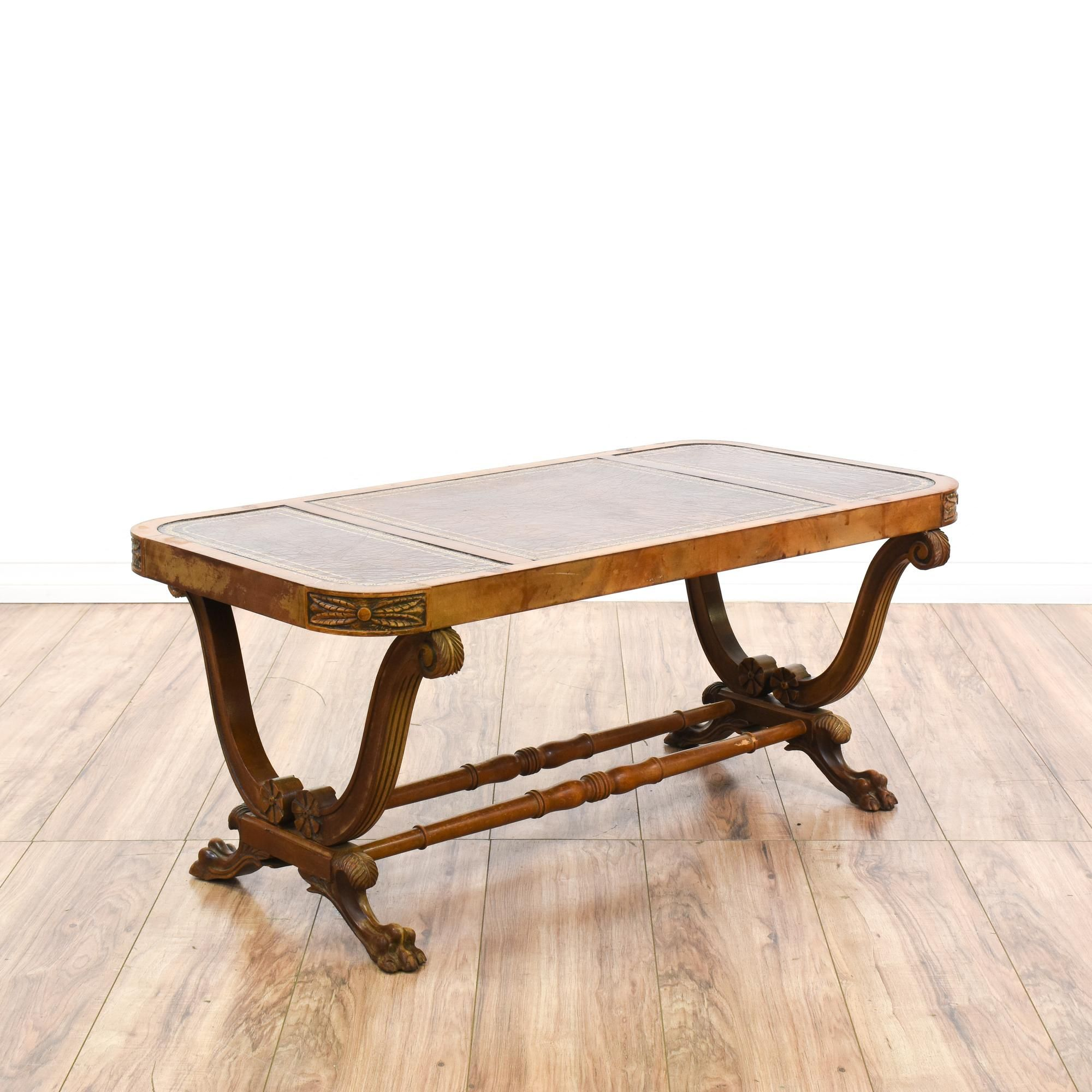 This ornate coffee table is featured in a solid wood with a glossy