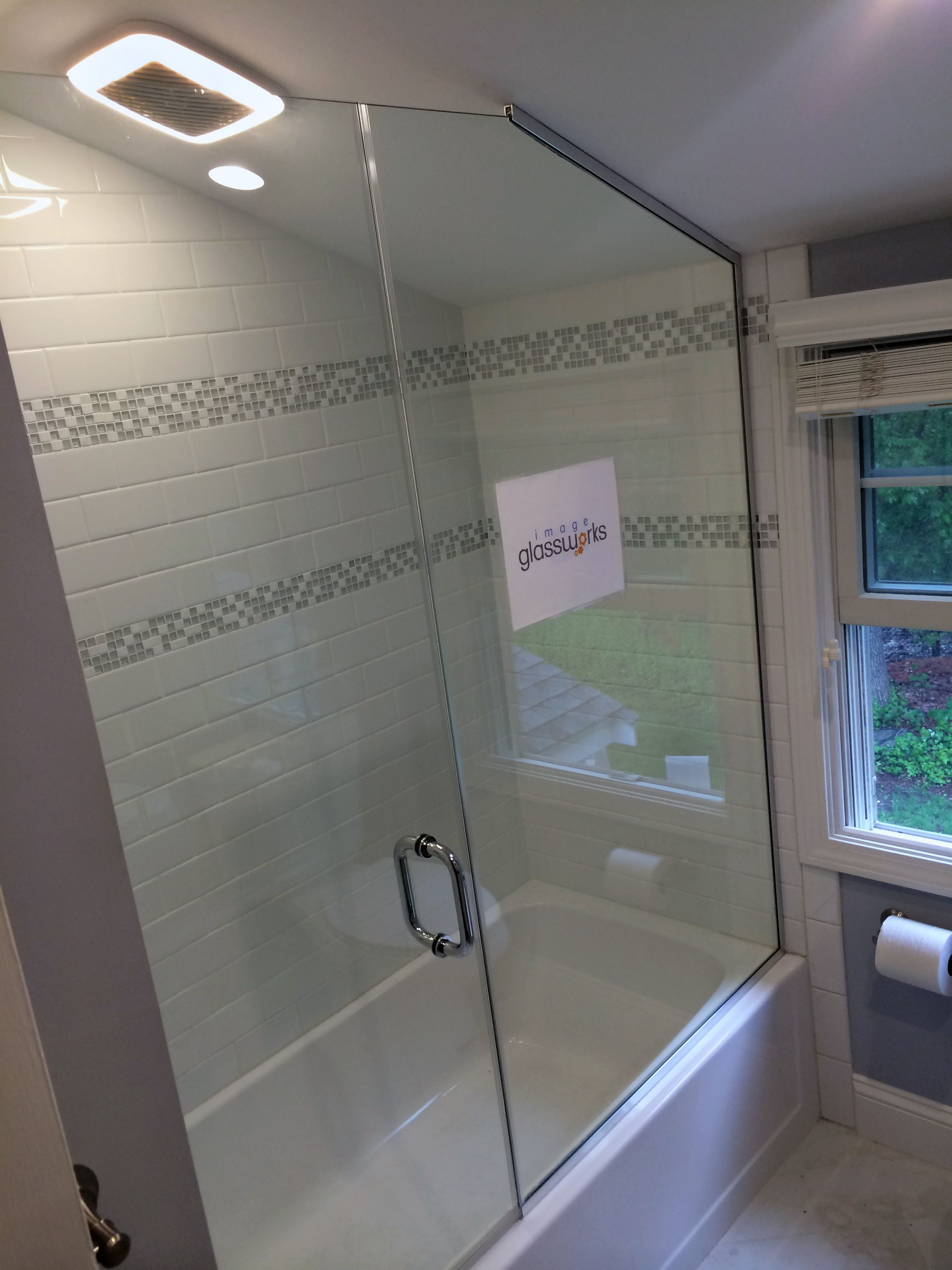 A simple shower door installed above a tub and butting a panel ...