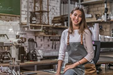 Female coffee shop owner sitting on the counter and smiling in camera