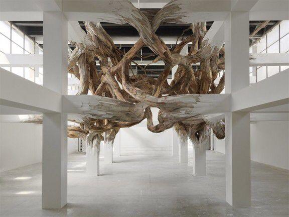 Henrique Oliveira, Vue de l'exposition «Baitogogo», dans le cadre de la saison «Nouvelles vagues», Palais de Tokyo, Paris.  «Baitogogo» s'impose à nous comme une impressionnante sculpture de bois composée à partir des piliers du Palais de Tokyo, qu'elle prolonge et démultiplie tout à la fois. Cette structure végétale foisonnante nous revoie alors vers un système complexe de rhizomes, et semble réanimer la matière morne des constructions architecturales. fleche suivante