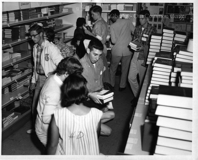 """ID#0211 Date: Unknown. This photo is of customers buying textbooks at the Co-op bookstore at 55 E. College St. This building was initially used only for the Co-op's book sales and school supplies but later housed some of its other businesses. Participant: Liz Burgess. Additional Sources: Oberlin Heritage Center: Fred Maddock files; McQueen, Albert, """"A Brief History of the Oberlin Consumers Cooperative and its Businesses.""""; Inge, Angela. """"A long Co-op History"""" Chronicle-Telgram, June 18…"""
