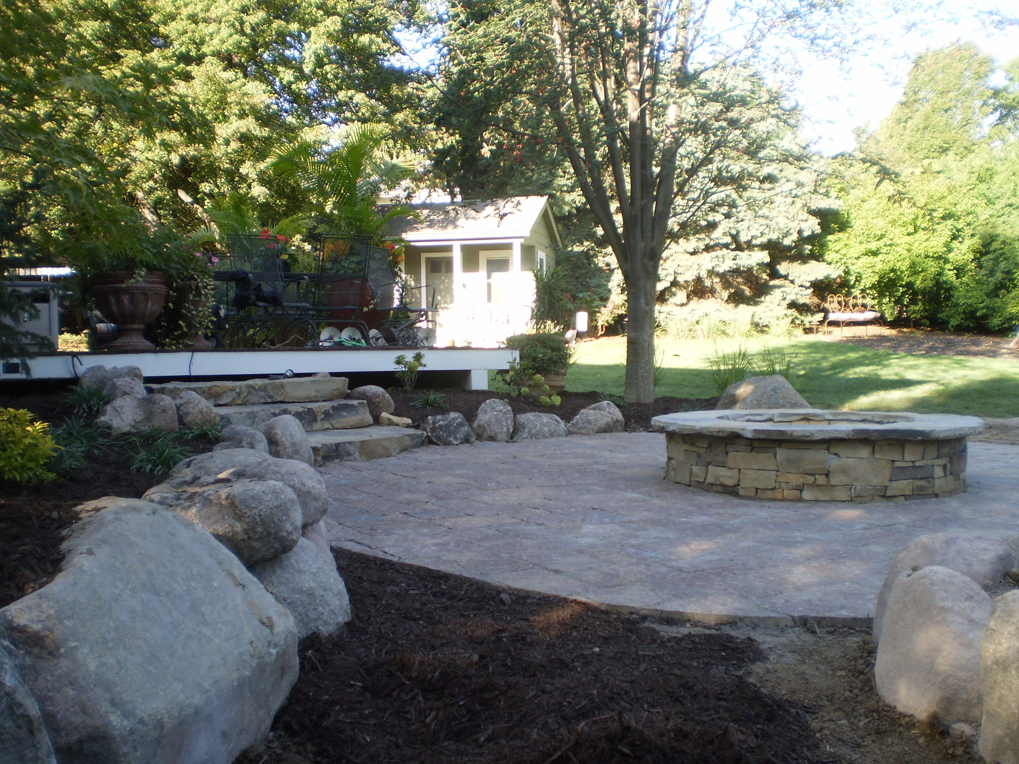 boulders and natural stone steps surround paver patio and fire pit