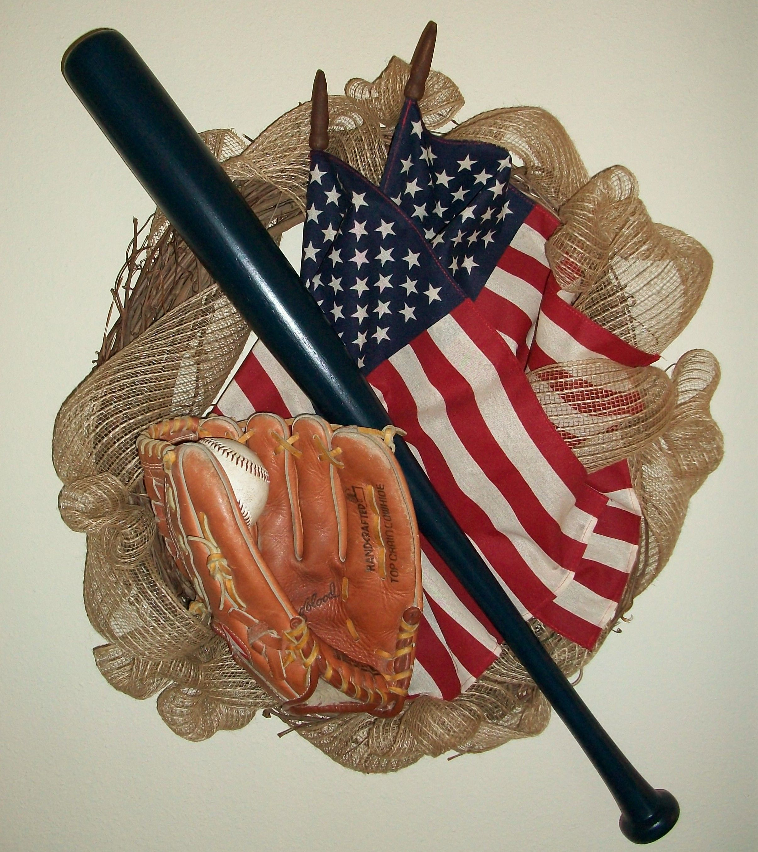 Batter up! Nothing says summer like the sound of the bat hitting a ball. For the baseball lover - this wreath is classic American spirit. American flags on a grapevine wreath with burlap, authentic wood bat, leather glove, and real ball.  MLB, Little League, Legion Baseball, Americana, Patriotic.