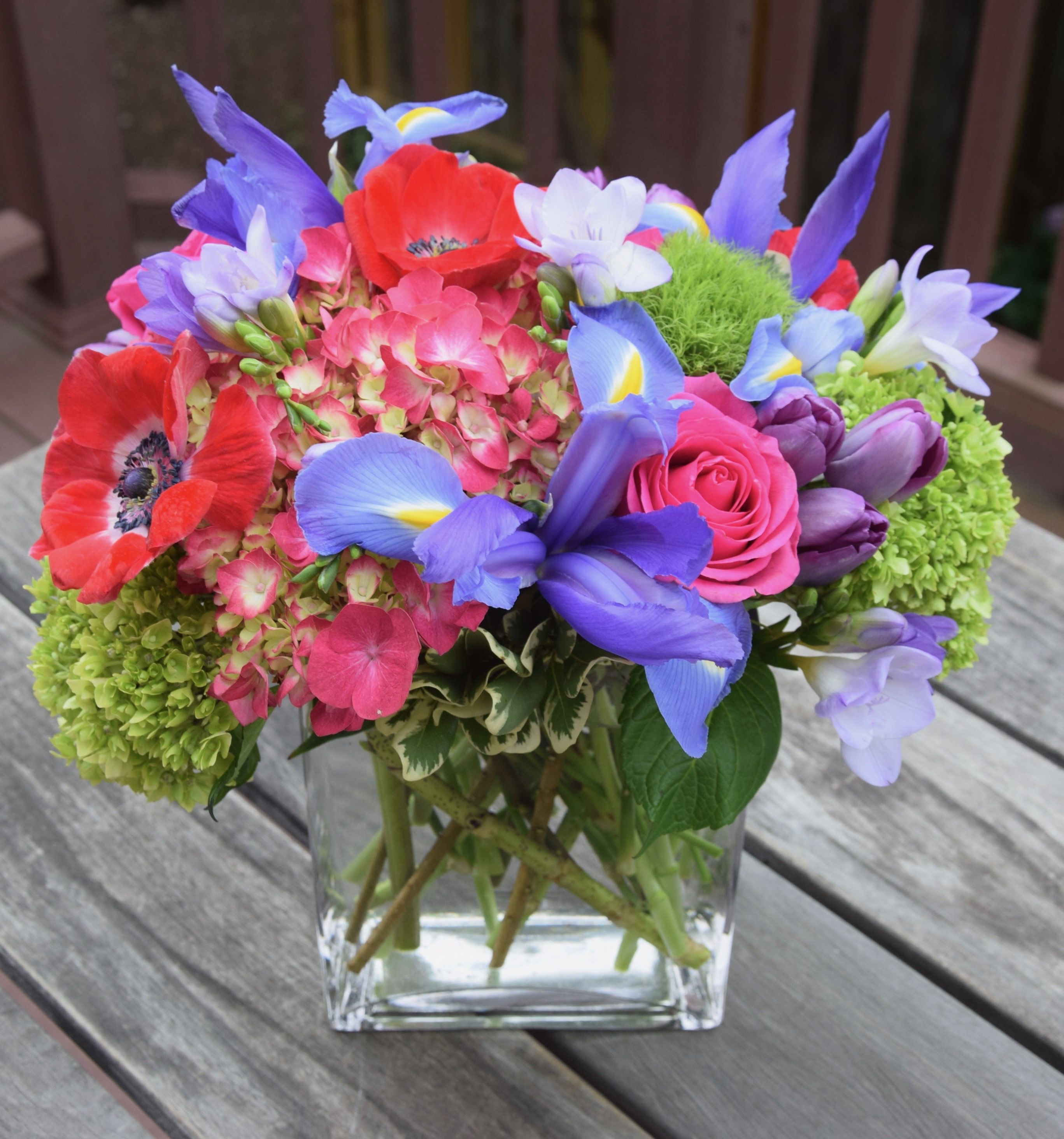 Flower Arrangement With Red Anemones Blue Irises Hydrangeas Tulips Freesia And Roses With Images Flower Arrangements Flower Delivery Fresh Flowers Arrangements