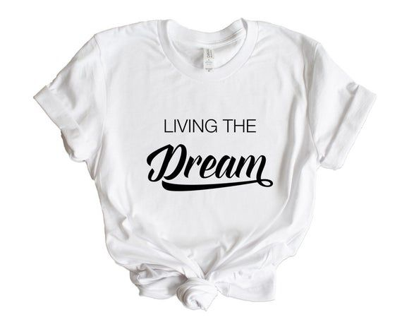 """""""Living The Dream"""" positive vibes unisex t-shirt for men and women.Funny, inspirational, motivational quote gift idea for an entrepreneur, self employed business owner.Whether you are side hustling or already successful, this is a funny statement design for you. Incredibly soft, vintage feel tee with a worn in feel you will love. Our quality shirts and tees are from Bella Canvas and is made of soft 100% premium ring-spun cotton. (Heather colours with 90/10 cotton/polyester- see colour options in"""