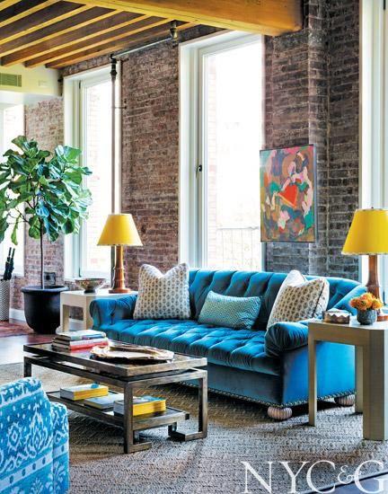 A custom tufted sofa covered in #Schumacher blue velvet   Tilton Fenwick Puts a Fresh Spin on a Traditional Artist's Loft in SoHo   New York Cottages & Gardens