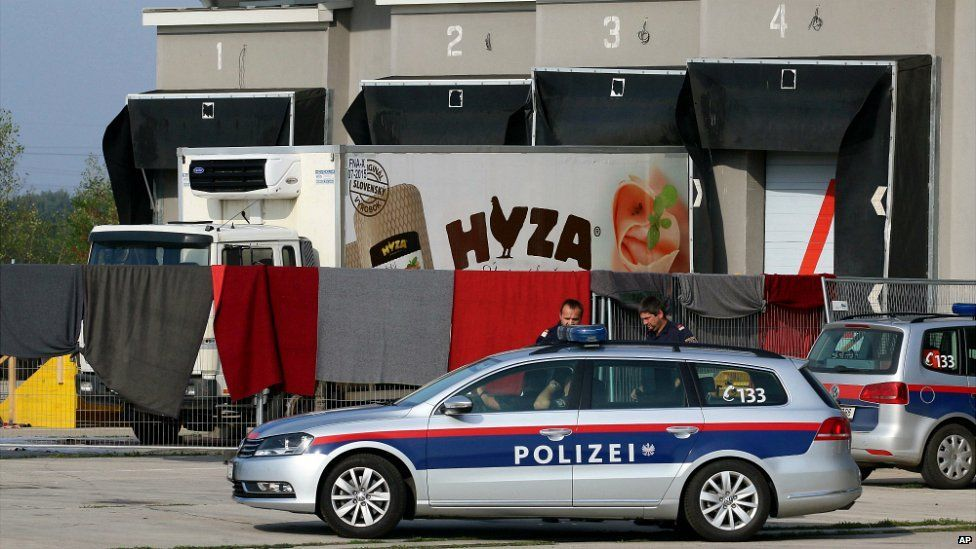 Blankets cover the view of a truck, which was found with the bodies of dozens of people inside, at a customs facility in Austria - 28 August 2015